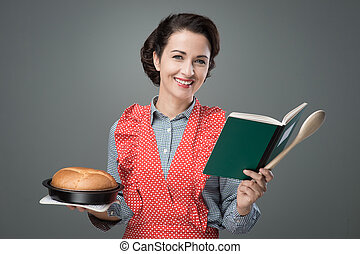Smiling retro housewife holding a cookbook and a baking tin with a homemade cake