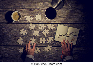 Retro image of a businessman, innovator or student looking for solution to his challenge or problem while metaphorically rearranging puzzle pieces and taking notes on his rustic wooden work desk and his table lamp turned on.