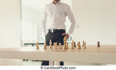 Retro image of a businessman standing proud next to his desk with chess figures on it