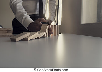 Retro image of a businessman stopping the domino effect with a sunlight
