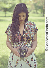 Retro image of beautiful woman holding vintage camera outdoors