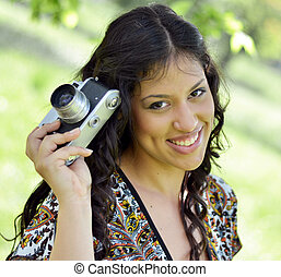 Retro image of beautiful woman holding vintage camera