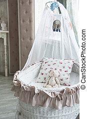 Retro interior children's bedroom with a wicker crib and teddy b