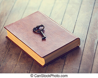 Retro key and opened book on wooden table.