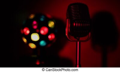 Retro microphone and colourful illumination sphere spin lit ...