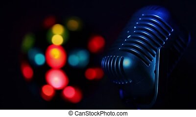 Retro microphone spins lit by color light at background of colourful spots