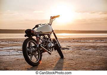 Retro motorcycle standing in the desert at sunset