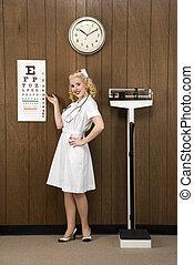 Retro nurse. - Caucasian mid-adult female nurse pointing to...