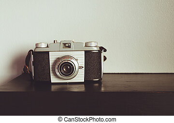 Retro old outdated rangefinder film camera from 50s on table front wall background. Vintage style filtered photo