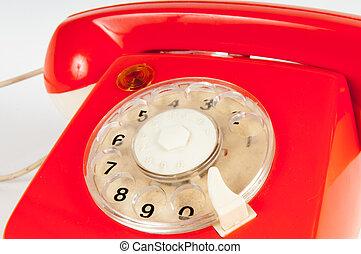 Retro orange telephone with rotary dial on white - Orange...