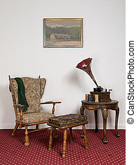 Retro ornate armchair, old phonograph, cylinders on round coffee table