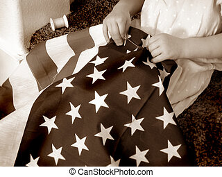 Sepia of child sewing an American flag (retro).