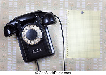 Retro phone and blank on a wooden wall