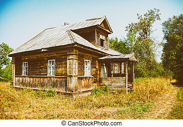 Retro photo with old wooden broken house in russian abandoned village in summer day