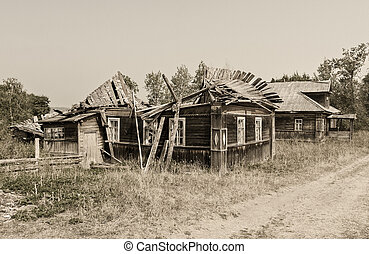 Retro photo with old wooden broken houses in russian abandoned village in summer day