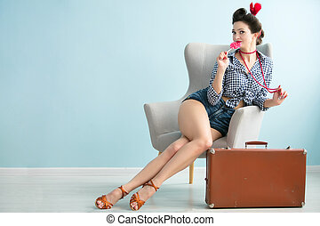 Retro pin-up girl with an old suitcase sits in a chair ..