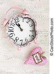 Retro pink clock and soft pink heart with word WISH on wooden background, top view, vertical composition