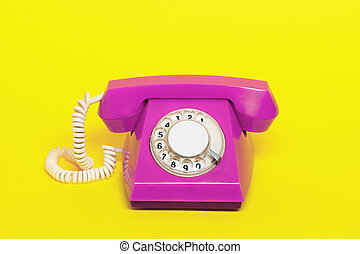 Retro pink phone on yellow.