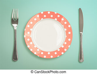 Retro polka dot plate with fork and knife top view