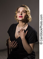 Retro portrait of beautiful woman in black dress sitting on the chair on gray background. Vintage style