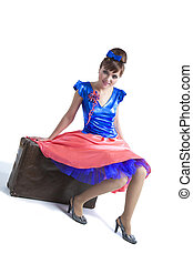 Retro portrait of woman sitting on suitcase