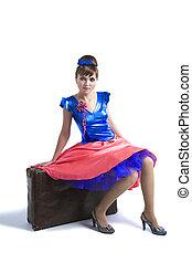 Retro portrait of woman sitting on suitcase