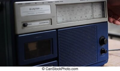Searching the favorite radio frequency on a eighties mono radio and cassette device.