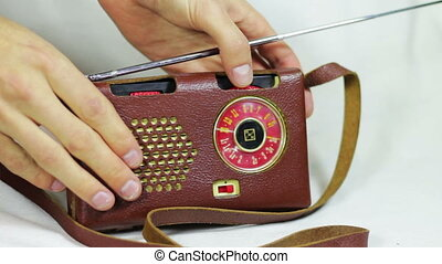 Tuning and search for radio stations on a portable old, vintage radio receiver in leather case.