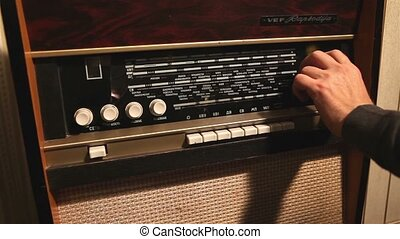 Retro radio, the man changes the frequency on the old radio receiver, the frequency change on the old receiver