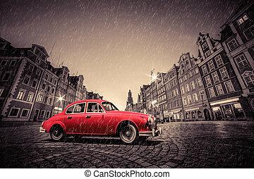 Retro red car on cobblestone historic old town in rain....