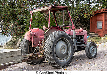 Retro red old tractor with a chariot along the road