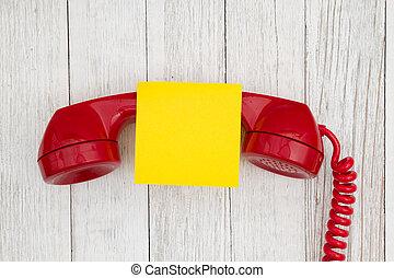 Retro red phone handset on weathered whitewash textured wood background