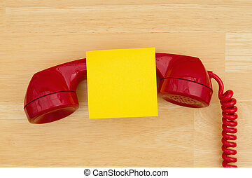 Retro red phone handset with sticky note on textured wood desk