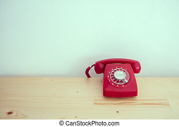 Retro red rotary telephone on wood table