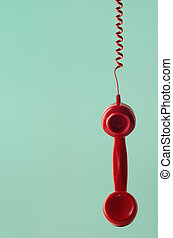 Retro Red Telephone Receiver Hanging by Spiral Cord on Aqua Background