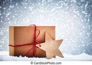 Retro rustic Christmas gift, present in snow on glitter background