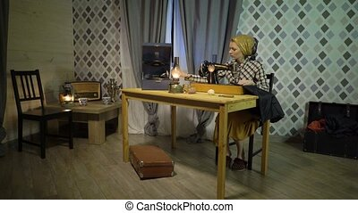 Retro seamstress girl sews cloth with old manual hand sewing machine. Woman working at home or workshop at night with kerosene lamp, listens music on gramophone or phonograph with vinyl plate