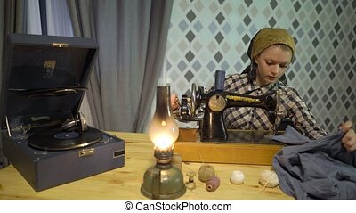 Retro seamstress girl sews cloth with old manual hand sewing machine. Woman works at home or workshop at night with kerosene lamp, listens music vinyl plate, gramophone or phonograph