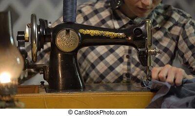 Retro seamstress girl sews cloth with old manual hand sewing...