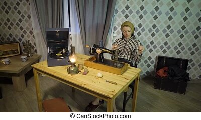 Retro seamstress girl winding threads, enjoys work, sews with old manual hand sewing machine. Woman working at home or workshop at night with kerosene lamp, listens music on gramophone phonograph