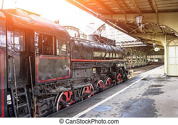 Retro steam locomotive train stands on the railway station.