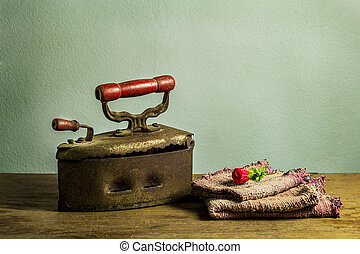 Retro still life with old rusty iron on wooden