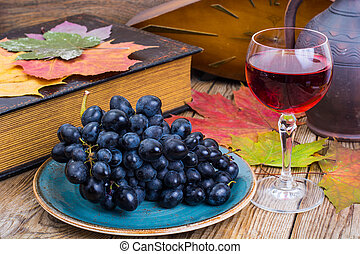Retro still life with red wine, book, watch and grape