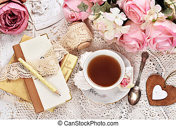 retro style flatlay of tea, bunch of flowers and laces -...
