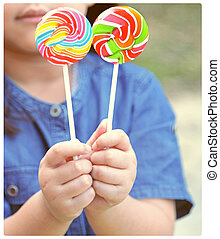 Retro style, hand holding lollipops