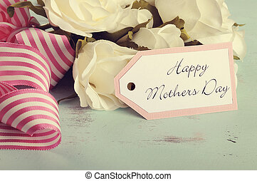 Retro style Happy Mothers Day gift of white roses bouquet with pink stripe ribbon and gift tag with greeting on aqua blue vintage shabby chic table.