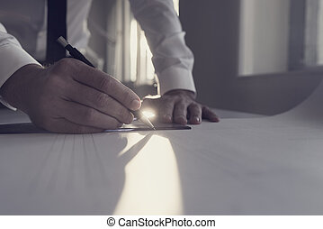 Retro style image of an architect working at a table in an office backlit by a bright sunlight