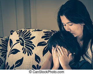 Retro style of sad little boy being hugged by his mother at home. Parenthood, Love and togetherness concept.