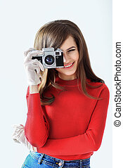 Retro style portrait of young beautiful woman taking photo with camera