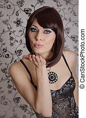 Retro styled brunette in corset sending kisses